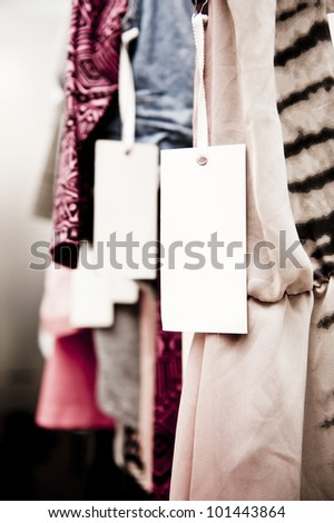 tight crop of clothes in a boutique with a blank tag, ready for your quirky copy. - stock photo