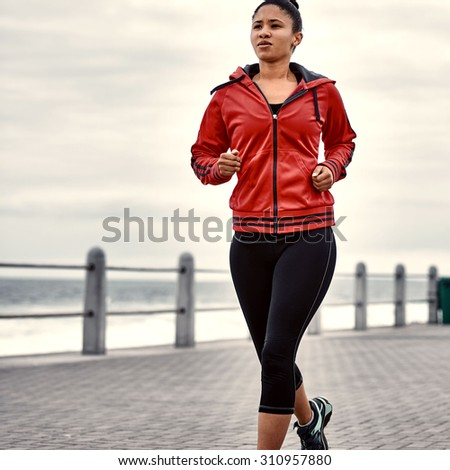 Tightly cropped square image of a young talented athletic female runner busy taking her morning job along the ocean side on the paved walk way - stock photo