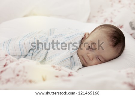Tightly sleeping baby boy on his side with pillow and blanket. - stock photo