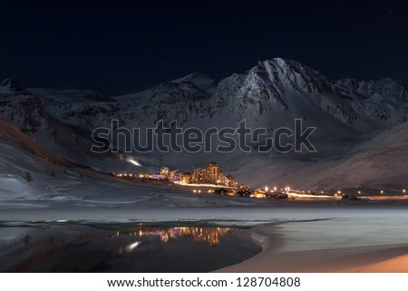 Tignes Val Clares at night shines in surrounded by mountain peaks - stock photo