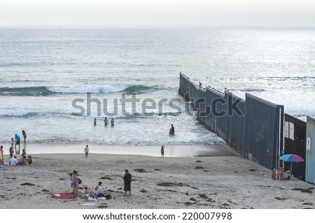 TIJUANA, MEXICO - JULY 26, 2014: Beach goers enjoy a day at the beach along the border fence in Tijuana, Mexico on a summer day - stock photo