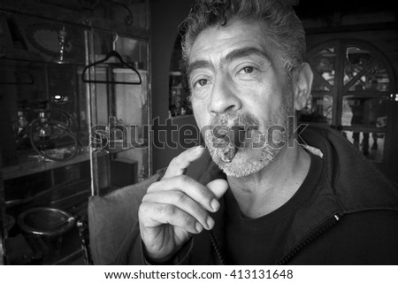 TIJUANA, MEXICO - MAY 27, 2015: A Tijuana cigar shop owner enjoys one of his store's popular Cuban cigars.  These cigars are banned across the border in the United States. - stock photo