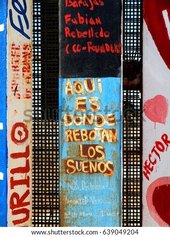 Tijuana, Mexico - September 5, 2015: Aqui es donde rebotan los suenos which translates as 'here is where the dreams bounce'. Spanish text painted on Mexico side of border fence between Mexico and USA.
