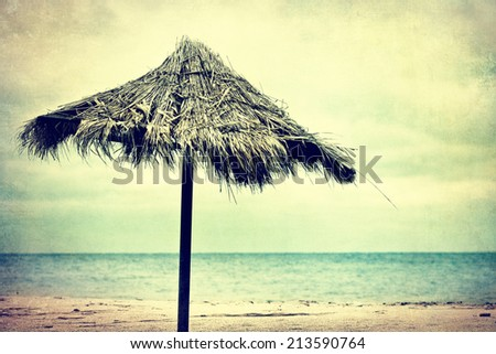 Tiki hut on the beach - textured old paper background - stock photo