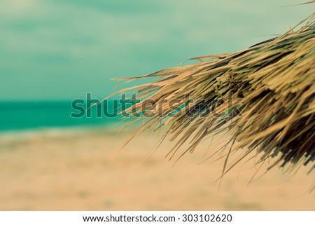 Tiki hut on the beach - textured old paper background - stock photo
