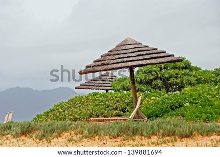 Tiki Hut Umbrella and Lounge Chairs in Tropical Kauai Hawaii Beach - stock photo
