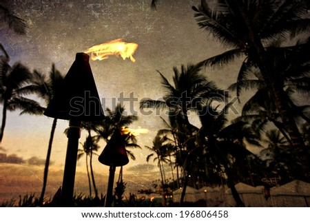 Tiki lanterns light the way on the beach at this resort in Wailea on Maui.  This image has a texture overlay for a vintage feel. - stock photo