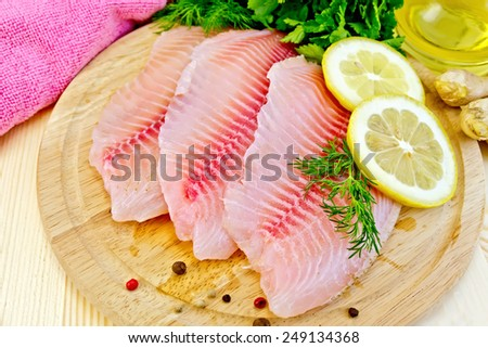 Tilapia fillets with dill, lemon, ginger, cloth, vegetable oil in a decanter on a wooden boards background - stock photo