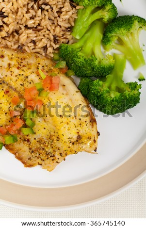 Tilapia Fish with Broccoli and Brown Rice. Selective focus. - stock photo