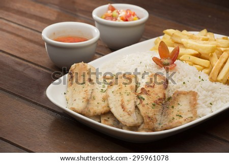 Tilapia portion with rice and fries - stock photo