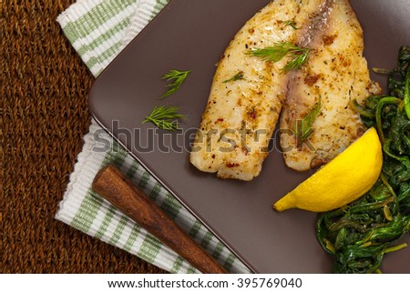 Tilapia with Sauteed Spinach. Selective focus. - stock photo