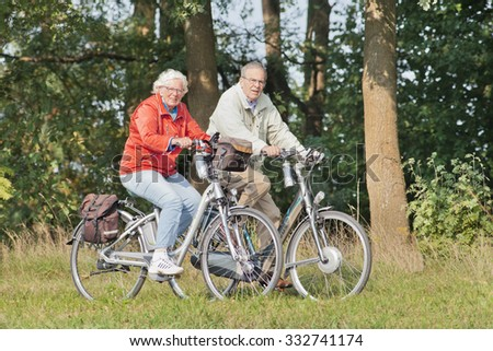 TILBURG-HOLLAND-OCT. 4, 2015. Elderly couple on e-bikes. 2014 e-bike sales raised with 16% and the Dutch expected a slowdown in 2015. But in the first two quarters sales increased with bigger numbers. - stock photo