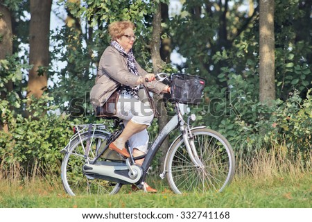 TILBURG-HOLLAND-OCT. 4, 2015. Elderly woman on Sparta e-bike. Sparta is a Dutch bicycle manufacturer based in Apeldoorn. It also produced motorcycles and scooters and is Europe's largest e-bike maker. - stock photo