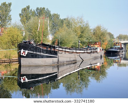 TILBURG-HOLLAND-OCTOBER 4, 2015. Old vessel moored in Pius Harbor with autumn color vegetation. It is one of the boats with a permanent berth in the Pius Harbor as part of an open-air maritime museum.