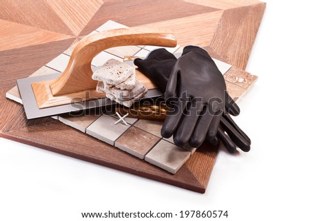 Tile, trowel, rubber gloves, decorative tiles, a cross on a white background - stock photo