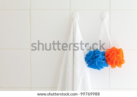 Tiled bathroom wall with towel on one hook and facecloth on another.