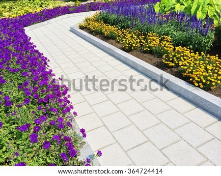 Tiled path in a summer garden with blooming purple and yellow flowers.