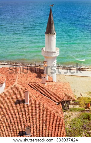 Tiled Roof with Minaret against the Sea - stock photo