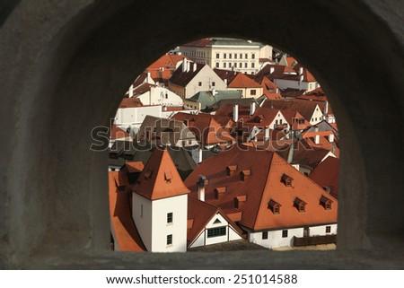 Tiled roofs seen through the wall of the castle garden in Cesky Krumlov, South Bohemia, Czech Republic. - stock photo