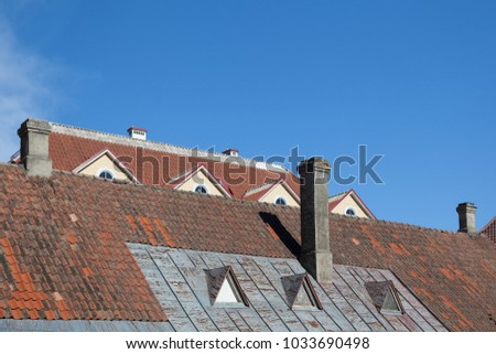 Tiled roofs with chimneys against the sky