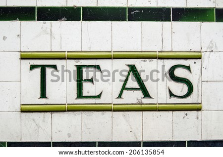 Tiled sign for Teas outside a disused cafe in London, UK.