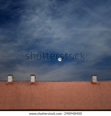 tiled top of the roof, cloudy blue sky and the moon at night - stock photo