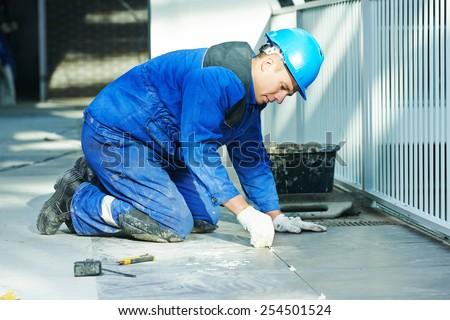 tiler builder worker installing floor tile at repair renovation work - stock photo