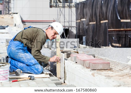 Tiler builder worker with level measuring marble tiles installation during construction works - stock photo