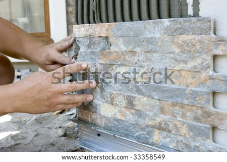 tiler install ceramic tile on wall - stock photo