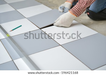 Tiler install ceramic tiles on a floor - stock photo