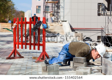 Tiler laborer monitoring quality of construction works during installation granite tiles - stock photo