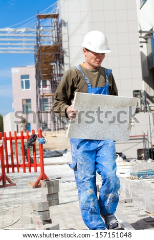 Tiler worker in helmet with granite tile at construction site - stock photo