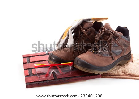 Tiles, boots for work, goggles and gloves on a white background