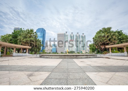 Tiles floor pavement plaza in Bangkok city Benchakitti Park with modern office building background  - stock photo
