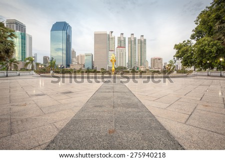 Tiles floor pavement plaza in Bangkok city Benchakitti Park with modern office building background in the evening - stock photo