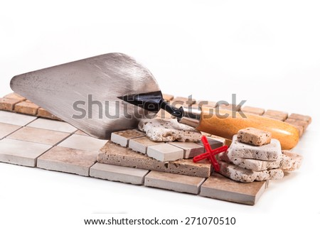 Tiles made of stone, marble and ceramics, trowel on a white background - stock photo
