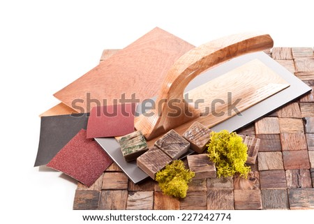 Tiles made of wooden blocks,trowel, sandpaper and moss on a white background - stock photo