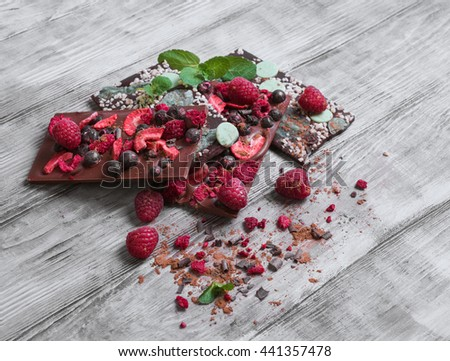 Tiles of broken exquisite hand-made chocolate with red dried and fresh berries, with green Ingredients nuts, peel, mint, cocoa powder, chips - stock photo