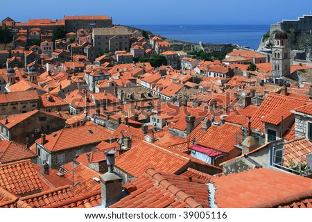 Tiles of old city roofs and the sea on the horizon