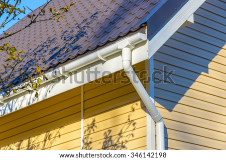 Tiles on the roof and rain gutter  on the house upholstered with siding. - stock photo