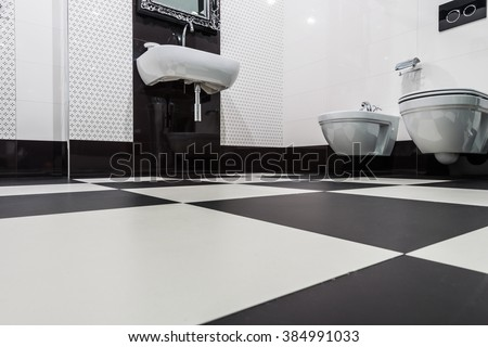 Tilled floor in modern bathroom interior black and white
