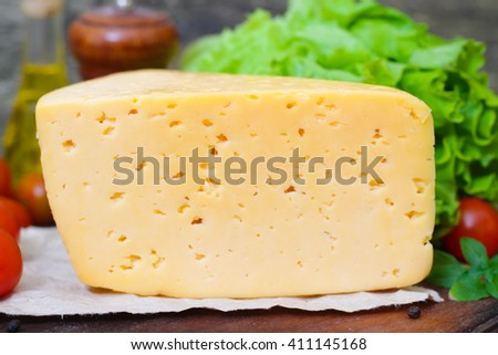 Tilsit Tilsiter cheese of the semi-hard cheese with vegetables on a wooden background - stock photo