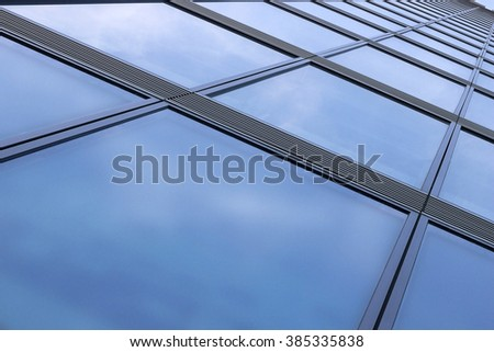 Tilt bottom view of structural glass wall of modern office building reflecting blue sky with clouds. Merger of contemporary architecture and the sky. Eco-friendly technologies. - stock photo