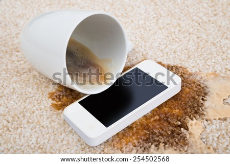 Tilt Coffee Cup Over Cellphone On Dirty Carpet - stock photo