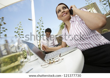 Tilt image of a business woman communicating on cell phone with man in the background