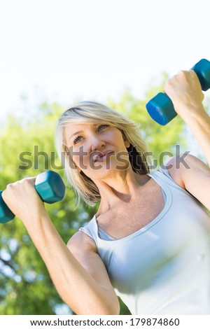 Tilt image of woman lifting dumbbells in the park - stock photo