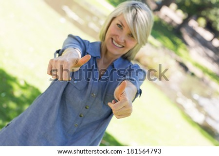 Tilt image of woman showing thumbs up gesture in a park