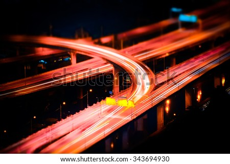Tilt shift blur effect. Abstract cityscape background. Futuristic night aerial view of highway interchange with moving cars. Bangkok, Thailand