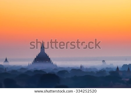 Tilt Shift blur effect. Amazing misty sunrise colors and silhouette of ancient Myauk Guni Pagoda. Architecture of ancient Buddhist Temples at Bagan Kingdom. Myanmar (Burma) travel destinations  - stock photo