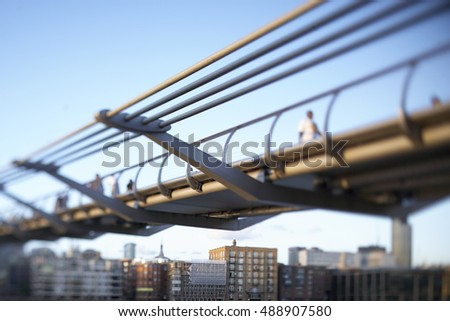 Tilt Shift image of the iconic Millennium Bridge spanning the River Thames under blue skies